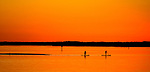 Paddleboarders work their way back to shore as the tide falls during sunset at Shell Point Beach south of Tallahassee.