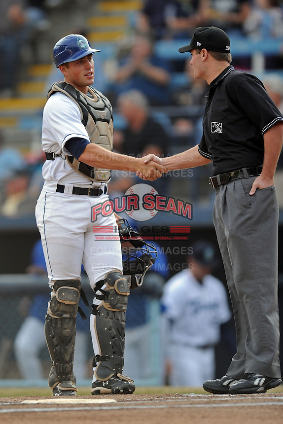Asheville Tourists catcher Tom Murphy #9 greets umpire Blake Carnahan before a game between the Lexington Legends and the Asheville Tourists at McCormick Field on April 23, 2013 in Asheville, North Carolina. The Tourists won the game 4-3. (Tony Farlow/Four Seam Images).