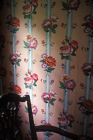 Edge of wooden chair in front of floral wallpaper<br />