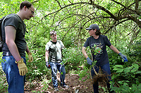 Kristine Jones (from right), volunteer coordinator with the city of Fayetteville Parks and Recreation, removes a bush honeysuckle Friday, June 4, 2021, with Nate Weston, geospatial ecologist with the Beaver Watershed Alliance, and volunteer Seth Carney at Kessler Mountain Regional Park. The Alliance partnered with the city to teach volunteers how to identify the highly invasive plant, that was introduced from Asia in the 1800's, and how to remove it. Check out nwaonline.com/210605Daily/ and nwadg.com/photos for a photo gallery.<br /> (NWA Democrat-Gazette/David Gottschalk)