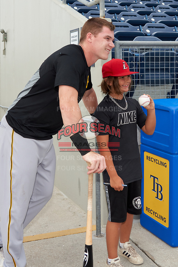FCL Pirates Black Henry Davis (32) poses for a photo with a young fan after signing a baseball before a game against the FCL Rays on August 3, 2021 at Charlotte Sports Park in Port Charlotte, Florida.  Davis was making his professional debut after being selected first overall in the MLB Draft out of Louisville by the Pittsburgh Pirates.  (Mike Janes/Four Seam Images)