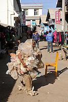 CHINA Yunnan, Yongningxiang, market, man dressed with plastic garbage / CHINA Yunnan, Yongningxiang, Markt, Mann mit Plastikmuell bekleidet