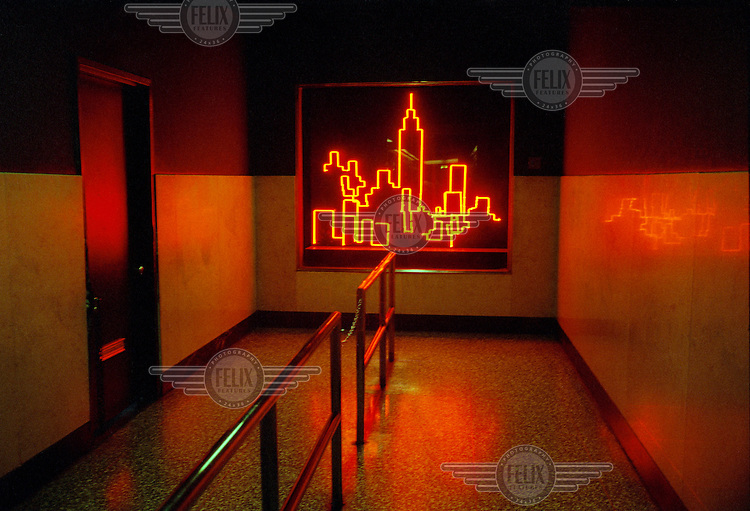 A neon skyline hangs on the wall of an apartment building in New York City.