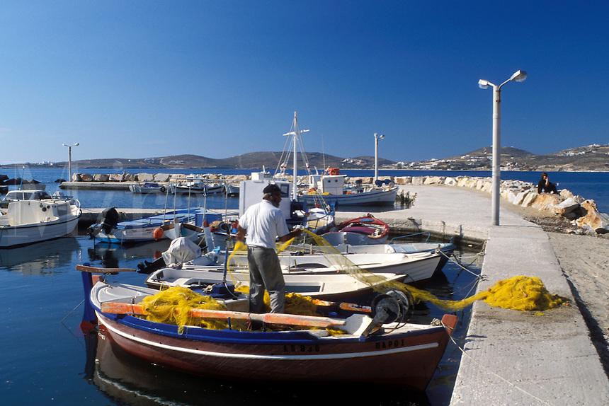 Paros, Greek Islands, Parikia, Cyclades, Greece, Europe, Fisherman pulling net onto fishing boat docked in the harbor of Parikia on Paros Island on the Aegean Sea.