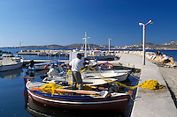 Paros, Greek Islands, Parikia, Cyclades, Greece, Europe, Fisherman pulling net onto fishing boat docked in the harbor of Parikia on Paros Island on the Aegean Sea.