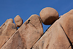 Round boulders caught in the crevasses of larger rocks at Joshua Tree.