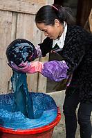 Huanggang, Guizhou, China.  A Dong Ethnic Village.  Woman Stirring Indigo Dye.