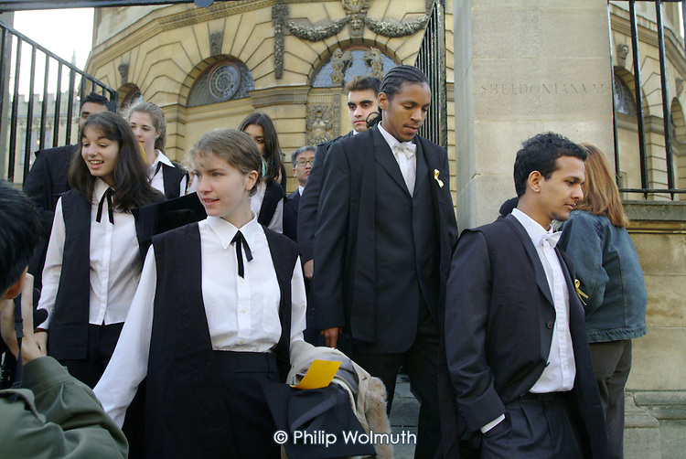 First year students at Oxford, some wearing gold ribbons in protest at tuition fees, leave the Sheldonian Theatre after matriculation, the ceremony which marks their formal induction as members of the university.