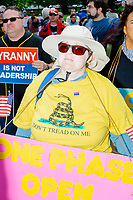 """A person wears a Gadsden flag t-shirt and holds a sign reading """"One phase open now"""" as people gather for an anti-lockdown protest organized by the alt-right group Super Happy Fun America near the home of Massachusetts governor Charlie Baker in Swampscott, Massachusetts, on Sat., May 16, 2020. The protest was in defiance of Massachusetts orders mandating face coverings and social distancing and prohibiting gatherings larger than 10 people during the ongoing Coronavirus (COVID-19) global pandemic. The state's stay-at-home order is expected to be updated on May 18, 2020, with a phased reopening plan issued by the governor as COVID-19 cases continue to decrease. Anti-lockdown protests such as this have become a conservative cause and have been celebrated by US president Donald Trump. Many of the protestors displayed pro-Trump messages or wore Trump campaign hats and shirts with phrases including """"Trump 2020"""" and """"Keep America Great."""" Super Happy Fun America, organizers of the protest, are an alt-right organization best known for creating the 2019 Boston Straight Pride Parade."""