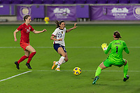 ORLANDO CITY, FL - FEBRUARY 18: Christen Press #23 takes a shot while pressured by Gabrielle Carle #14 and Stephanie Labbé #1 during a game between Canada and USWNT at Exploria stadium on February 18, 2021 in Orlando City, Florida.
