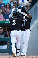 Luis Gonzalez (2) of the Charlotte Knights high fives teammate Yermin Mercedes (24) after hitting a 2-run home run against the Gwinnett Stripers at Truist Field on July 15, 2021 in Charlotte, North Carolina. (Brian Westerholt/Four Seam Images)