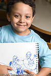 Education Preschool 4-5 year olds art activity proud boy showing his drawing recognizable human figures vertical