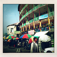 A hotel building with bright green balcony railings stands over a line of colourful umberellas that protect stall holders from the sun.