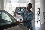 Jeremiah Munyi cleans the cars in the showroom at DT Dobie, Nairobi's elite car dealership. DT Dobie sells new Mercedes-Benz, Nissan, and Jeep to high end customers.