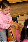 Preschool  vertical 3-4 year olds two girls playing together  with wire and bead toy