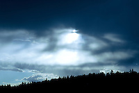 Sun setting in dark blue skies over the Kootenai National Forest in Montana