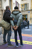"""Switzerland. The Republic and Canton of Neuchâtel. Neuchâtel. Downtown. Narcotics squad. """"Narko"""" operation. Three police officers on duty (both in plain-clothes) arrest a drug dealer from Western Africa and his customer. The convict black man is handcuffed because he was caught selling illegal drugs (cocaine) in the streets. Plainclothes law enforcement is a method used by police. The policemen wear plainclothes or """"ordinary clothes"""" instead of a uniform in order to avoid detection or identification as law enforcement agents. Police officers in plainclothes must identify themselves when using their police powers. 1.04.15 © 2015 Didier Ruef"""
