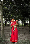 """A peasant Bengali girl holds her baby on Char Tilli island outside of Dhaka, Bangladesh.  A country subjected to many natural disasters, Char Tilli has been used by aid agencies to train for emergencies such as Cyclones , to have their staff ready to deal with the process required ..Citizens of  areas of Southern Bangladesh are resilient in the face of constant threat from nature and these portraits reflect the determination of the people to continue living their lives as they have done for generations. .The borders of present-day Bangladesh were established with the partition of Bengal and India in 1947, when the region became the eastern wing of the newly formed Pakistan. However, it was separated from the western wing by 1,600 km (994 mi) across India. Political and linguistic discrimination as well as economic neglect led to popular agitations against West Pakistan, which led to the war for independence in 1971 and the establishment of Bangladesh. After independence the new state endured famines, natural disasters and widespread poverty, as well as political turmoil and military coups. The restoration of democracy in 1991 has been followed by relative calm and economic progress..Bangladesh is the seventh most populous country and is among the most densely populated countries in the world with a high poverty rate. However, per-capita (inflation-adjusted) GDP has more than doubled since 1975, and the poverty rate has fallen by 20% since the early 1990s. The country is listed among the """"Next Eleven"""" economies. Dhaka, the capital, and other urban centers have been the driving force behind this growth. Recent (2005-2007) estimates of Bangladesh's population range from 142 to 159 million, making it the 7th most populous nation in the world. With a land area of 144,000 square kilometers, ranked 94th, the population density is remarkable. A striking comparison is offered by the fact that Russia's population is slightly smaller even though Russia has a land area of 17.5"""