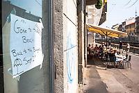"""Milano, cartello di chiuso per ferie (""""andati alla spiaggia, di ritorno agli hamburger il 2 settembre"""") sulla vetrina di un esercizio di ristorazione lungo il Naviglio Grande, a fianco di un ristorante aperto --- Milan, closed for vacation sign (""""gone to the beach back to the burgers sept 2nd"""") on the window of a eatery along the Naviglio Grande canal, next to an open restaurant"""