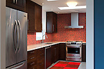 Blue dining room walls complement the bright red tile backsplash in this bold, contemporary kitchen remodel.