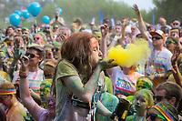 Girl Blowing Yellow Dye at The Color Run 2015 Music Concert, Seattle Center, Washington State, Wa, America, USA.