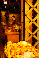 Woman selling nuts by streetlight.