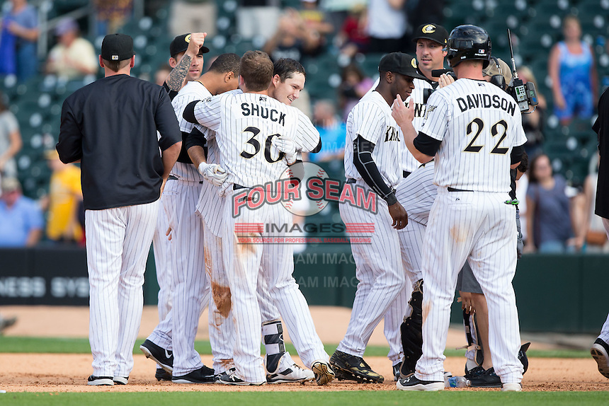 Jason Coats (17) of the Charlotte Knights gets a hug from teammate J.B. Shuck (30) after his walk-off single against the Gwinnett Braves in the bottom of the 11th inning at BB&T BallPark on May 22, 2016 in Charlotte, North Carolina.  The Knights defeated the Braves 9-8 in 11 innings.  (Brian Westerholt/Four Seam Images)