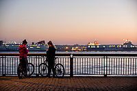 Two girls on bikes look at their phones on the waterfront at Liverpool, England, UK