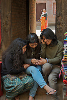 Nepalese teenage Girls texting on cellphone Bhaktapur, Layaku Nepal