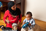 Toddler baby boy playing musical instruments with mother hitting tambourine with mallet while she plays drum