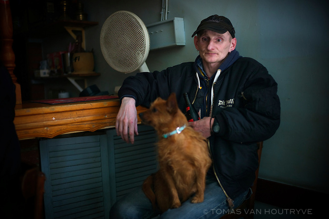 A man holds a dog on his lap inside a bar in the city of Lessines, Belgium on March 6, 2013.