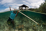 West Papuan fisherman with spear - split level with his outrigger houseboat. North Raja Ampat, West Papua, Indonesia