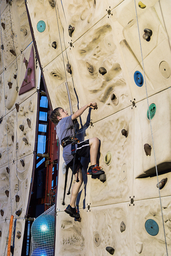 Boy scaling an indoor rock climbing wall.