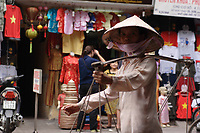 Hanoi<br /> , Vietnam - 2007 File Photo -<br /> <br /> <br /> A woman carrying baskets of goods walk in front of a colorful store display in hanoi.<br /> <br /> <br /> photo : James Wong-  Images Distribution