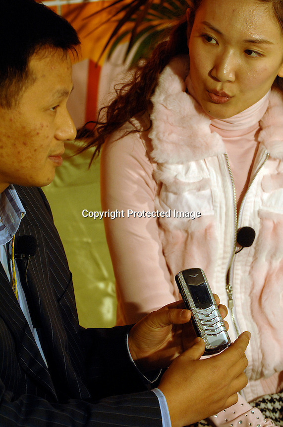 A man holds-up a Nokia Vertu jewellery phone encrusted with 900 small diamonds worth 200,000 rnb Chinese rnb at the Guangzhou Luxury Goods Fair in China.