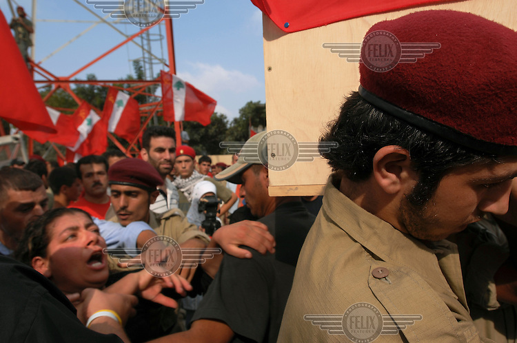 A Hezbollah (Hizbollah) fighter carries a coffin at a mass funeral in Srifa for 35 people whose bodies were found in the rubble over the previous three days. 170 houses in Srifa were levelled and 620 damaged beyond repair by Israeli bombardment during 34 days of conflict between Israel and Hezbollah.