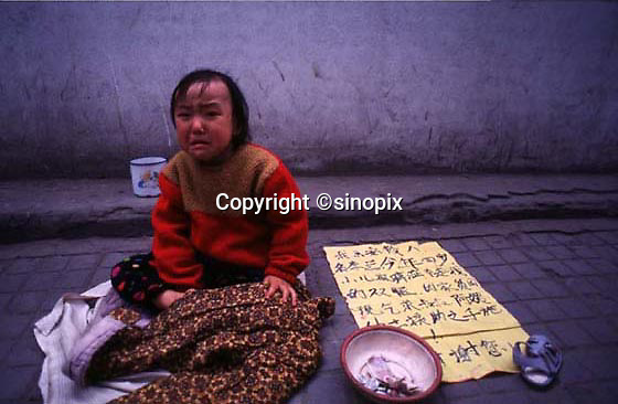 """A YOUNG GIRL SITS NEXT TO HER BEGGING BOWL AND A SIGN TELLING OF HER POVERTY IN FUZHOU CITY, FUJIAN PROVINCE CHINA  26.10.96.  MANY PEOPLE FLOCK TO THE CAPITAL OF FUJIAN TO PREY ON THE WEALTHY  AND YOUNG GIRLS WHO CAN BE BOUGHT RELATIVELY CHEAPLY ARE OFTEN USED AS BEGGING """"TOOLS"""".<br /> <br />  <br /> ONE CHILD POLICY/CHILDREN/POVERTY/FUJIAN"""