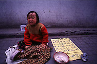 "A YOUNG GIRL SITS NEXT TO HER BEGGING BOWL AND A SIGN TELLING OF HER POVERTY IN FUZHOU CITY, FUJIAN PROVINCE CHINA  26.10.96.  MANY PEOPLE FLOCK TO THE CAPITAL OF FUJIAN TO PREY ON THE WEALTHY  AND YOUNG GIRLS WHO CAN BE BOUGHT RELATIVELY CHEAPLY ARE OFTEN USED AS BEGGING ""TOOLS"".<br /> <br />  <br /> ONE CHILD POLICY/CHILDREN/POVERTY/FUJIAN"