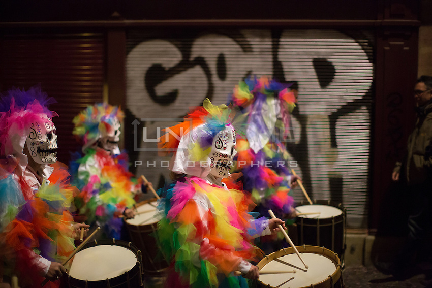 A 'clique' of masked participants in the Carnival of Basel, or Fasnacht, march along a street in the old town of Basel, Switzerland, while drumming, on the final night of festivities. Feb. 26, 2015.
