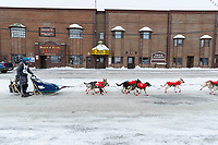 Justin Stielstra runs down Front Street with the Board of Trade Saloon in the background on the way to the finish line in Nome  during the 2017 Iditarod on Friday March 17, 2017.<br /> <br /> Photo by Jeff Schultz/SchultzPhoto.com  (C) 2017  ALL RIGHTS RESERVED