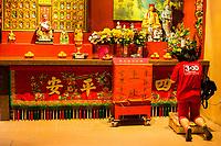 Woman Praying in a Side Altar in Guan Di (Kuan Ti) Taoist Temple, Chinatown, Kuala Lumpur, Malaysia.