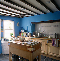 A blue country kitchen with a beamed ceiling. A blue and white tiled panel provides a splashback to the sink set on wooden units. A butcher block stands in the centre of the kitchen.