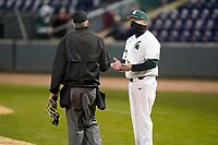 Head coach Jake Boss Jr. (23) of the Michigan State Spartans talk with home plate umpire Tim Catton in a game against the Maryland Terrapins on Saturday, March 6, 2021, at Fluor Field at the West End in Greenville, South Carolina. (Tom Priddy/Four Seam Images)
