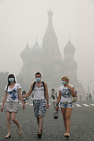 Moscow, Russia, 07/08/2010. .People in Red Square wear protective masks in the worst smog so far in the record high temperatures of the continuing heatwave. Peat and forest fires in the countryside surrounding Moscow have resulted in the Russian capital being blanketed in heavy smog.