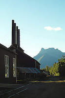 Mountains loom over the main street at Kennicott Mine. The power plant, with its distinctive chimneys, is on the left.