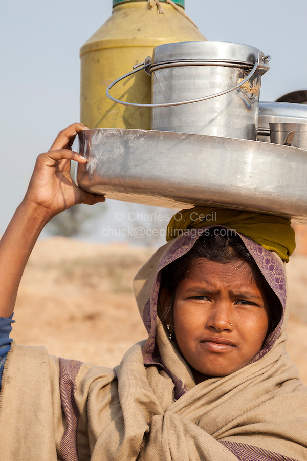 Rajasthan, India.  Young Girl Carrying Utensils on her Head.
