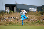 Philip Golding of England cleans his shoes on the 9th green during day one of The Senior Open Golf Tournament at The Royal Porthcawl Golf Club in South Wales this afternoon.