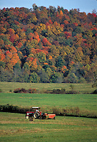 A tractor drives across farming land surrounded by fall foliage. Seen in the Blue Ridge Mountains area located in southwest Virginia. Abingdon Virginia.