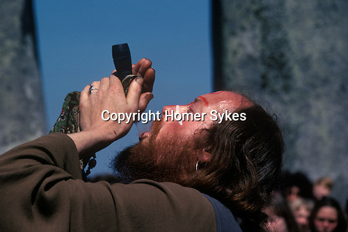 """Sid Rawle known as the King of the Hippies. 1970's style hippies attend the first free festival at Stonehenge to celebrate the summer solstice June 21st 1970's.Smoking a """"Peace Pipe""""."""