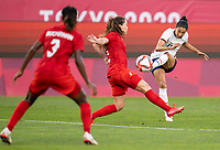 KASHIMA, JAPAN - AUGUST 2: Christen Press #11 of the USWNT takes a shot during a game between Canada and USWNT at Kashima Soccer Stadium on August 2, 2021 in Kashima, Japan.